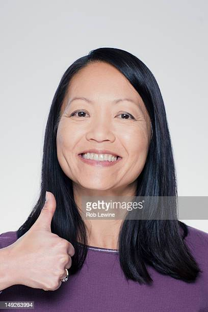 Studio portrait of mature woman showing thumbs up sign