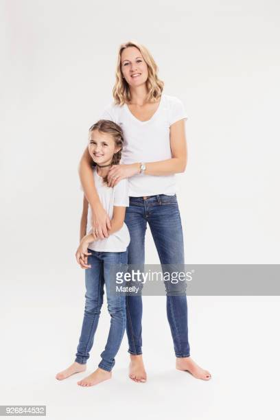 studio portrait of mature woman with daughter, full length - girls barefoot in jeans stock photos and pictures