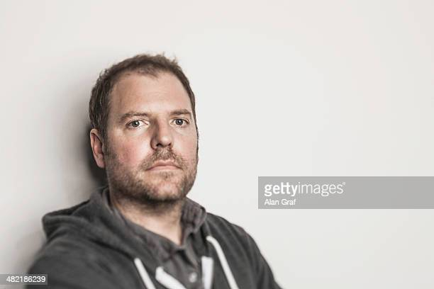 Studio portrait of mid adult man in hooded top