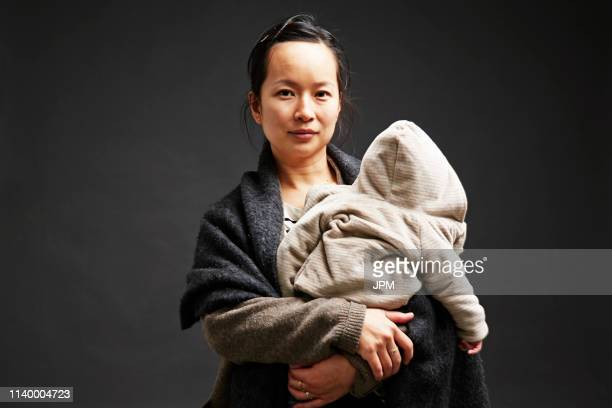 studio portrait of mid adult woman holding baby son - shawl stock pictures, royalty-free photos & images