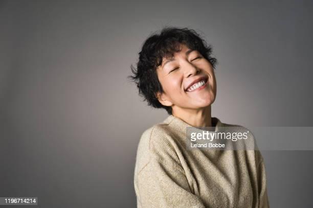 studio portrait of middle aged japanese woman - augen geschlossen stock-fotos und bilder