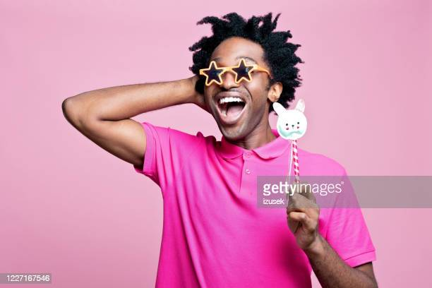 studio portrait of mischief young man wearing star shaped sunglasses - gesturing stock pictures, royalty-free photos & images