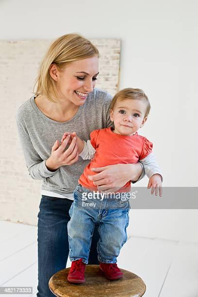 Studio portrait of mother holding baby daughter