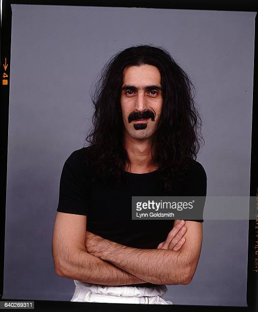 Studio portrait of musician Frank Zappa standing alone in a black teeshirt with his arms folded Undated color photo