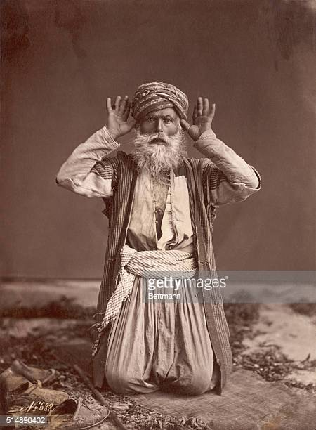 Studio portrait of Muslim man posed in prayer
