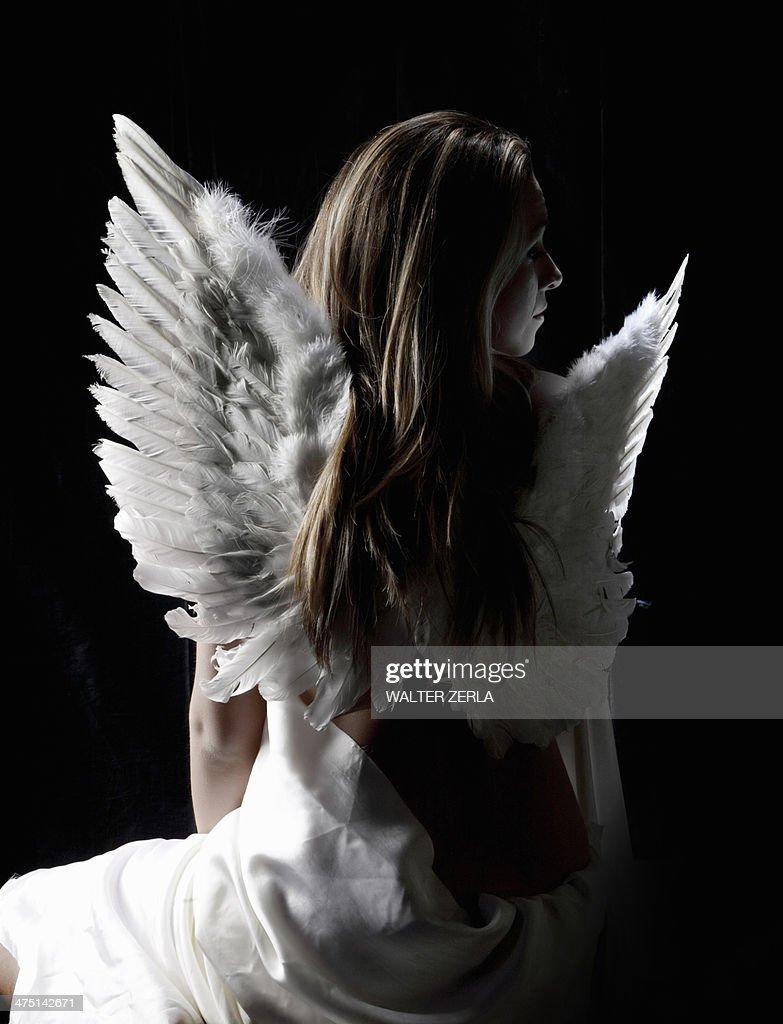 Studio portrait of pensive woman wearing angel wings : Foto de stock