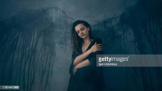 studio portrait of pensive woman with wings - ukrainian angel stockfoto's en -beelden