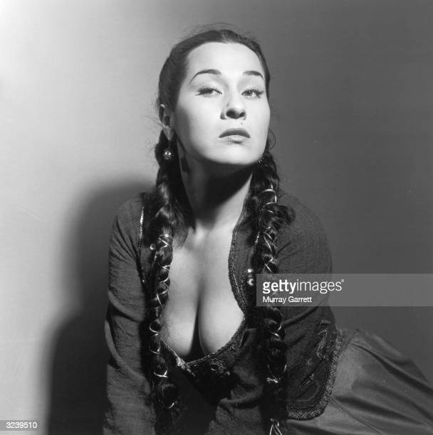 Studio portrait of Peruvianborn actor Yma Sumac wearing in a revealing peasantstyle dress with two braids falling over her shoulders Hollywood...