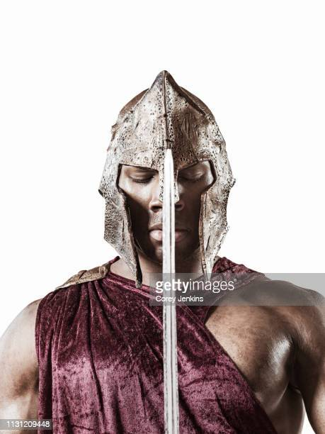 studio portrait of poised young man dressed as gladiator with helmet and sword - gladiator fotografías e imágenes de stock