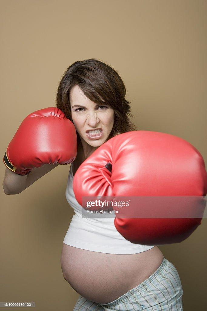 Studio portrait of pregnant woman wearing boxing gloves : Stockfoto