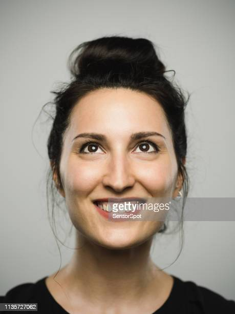 studio portrait of real mediterranean young woman with excited expression looking up - southern european descent stock pictures, royalty-free photos & images