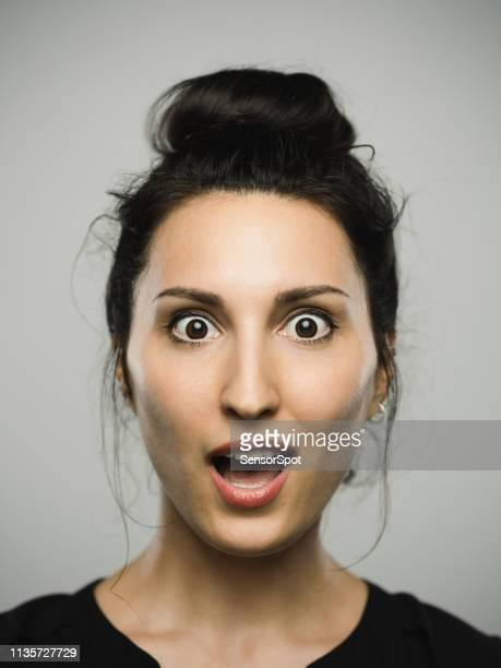 studio portrait of real mediterranean young woman with surprised expression - brown eyes stock pictures, royalty-free photos & images