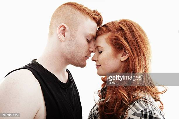 Studio portrait of red haired young couple head to head with eyes closed