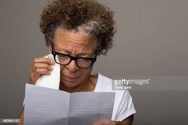 Studio portrait of sad senior woman reading a letter
