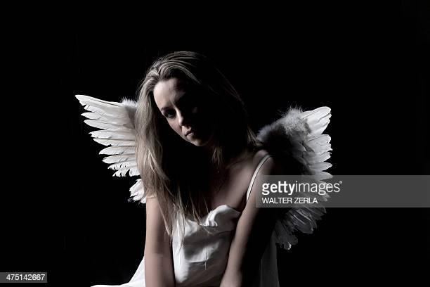 Studio portrait of sad woman wearing angel wings