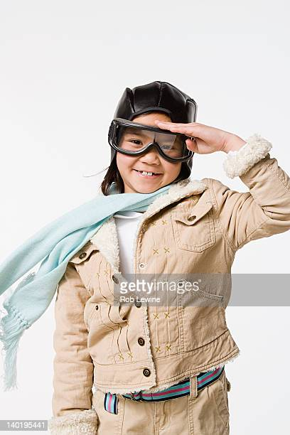 studio portrait of saluting girl (8-9) wearing aviator's cap and flying goggles - saluting stock pictures, royalty-free photos & images