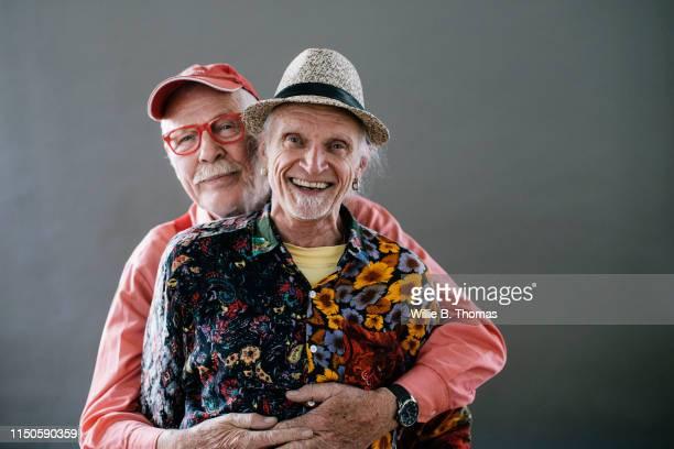 studio portrait of senior gay couple - gay seniors photos et images de collection