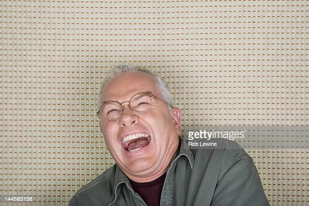 Studio portrait of senior man laughing