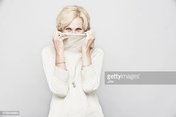 studio portrait of senior woman hiding behind roll neck - turtleneck stock pictures, royalty-free photos & images