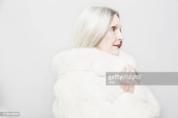 Studio portrait of senior woman in white fur coat
