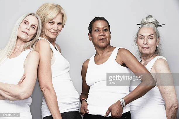 studio portrait of senior women friends posing for camera - tank top stock photos and pictures
