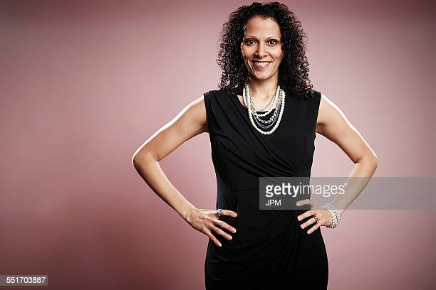 Studio portrait of smiling mature businesswoman with hands on hips