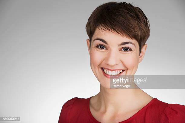 studio portrait of smiling woman with short hair - kurzhaarschnitt stock-fotos und bilder