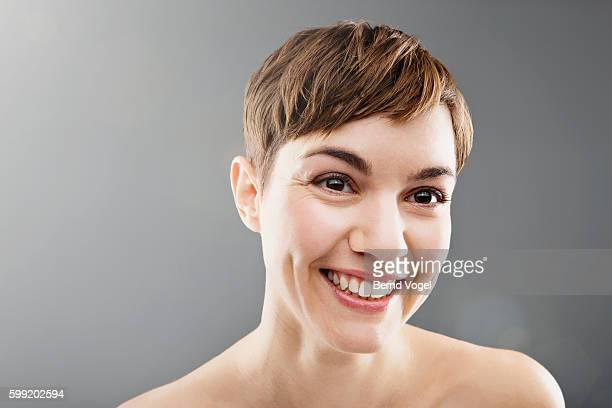 Studio portrait of smiling woman with short hair