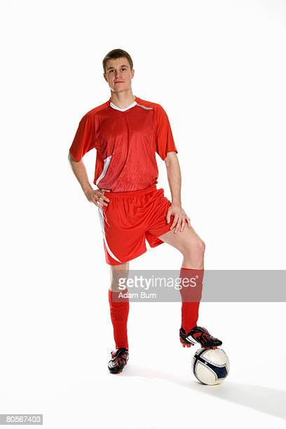 studio portrait of soccer player with his foot on a soccer ball - fußballspieler stock-fotos und bilder