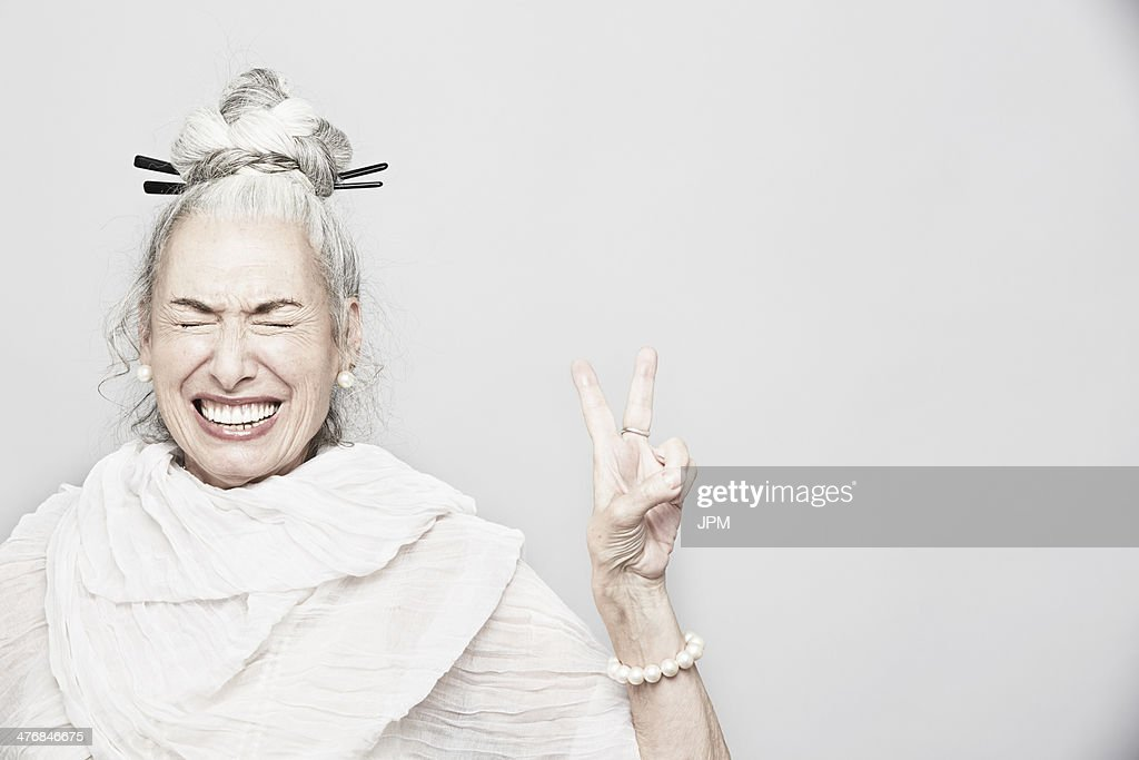 Studio portrait of sophisticated senior woman making victory sign : Stock Photo