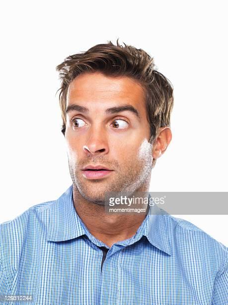 Studio portrait of surprised business man looking away