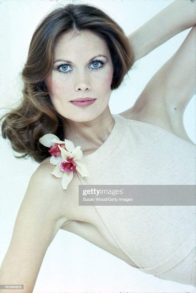 Studio portrait of Swedish model and actress Maud Adams as she poses, in a halter-neck dress, against a white background, April 1975.