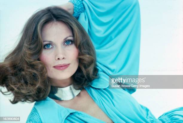 Studio portrait of Swedish model and actress Maud Adams as she poses in a blue outfit with a silver necklace against a white background April 1975