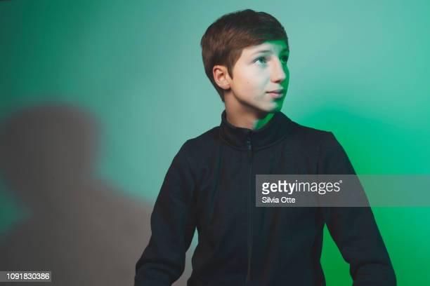 Studio Portrait of teenage boy, lit with green light