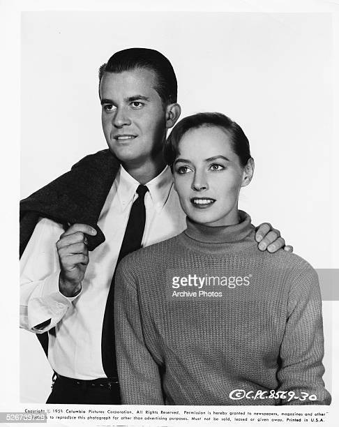 Studio portrait of television personality Dick Clark with his hand on a woman's shoulder for Columbia Pictures 1958