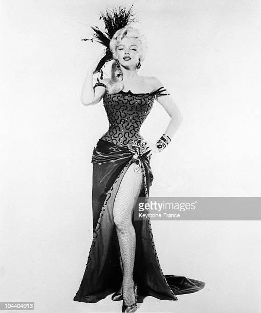 Studio portrait of the American starlet Marilyn MONROE in a long dress and fathers above her head.