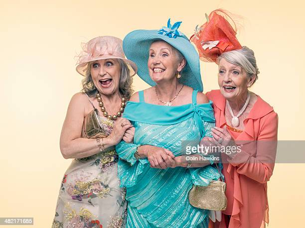 Studio portrait of three happy glamorous senior women