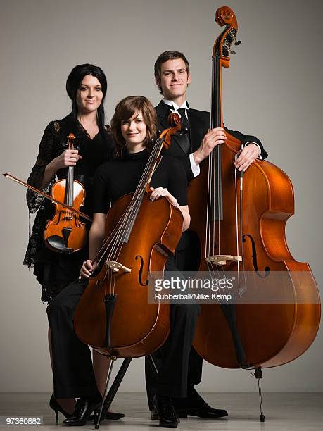 Studio portrait of three young musicians with instruments