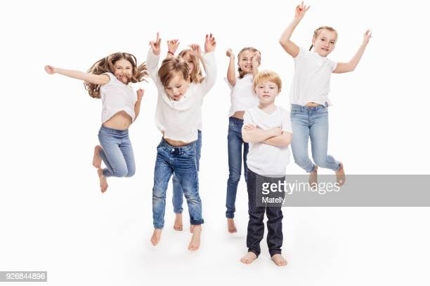 studio portrait of two boys and four girls having fun jumping mid air, full length - mittelgroße personengruppe stock-fotos und bilder
