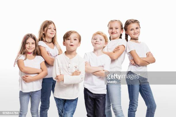Studio portrait of two boys and four girls posing with arms folded