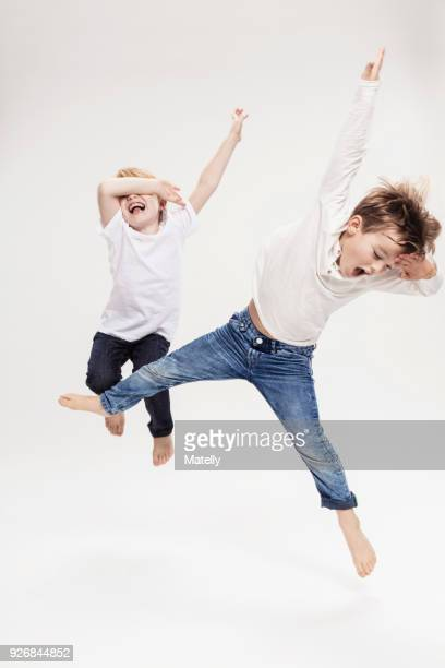Studio portrait of two boys having fun jumping mid air, full length