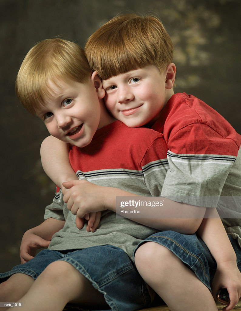 studio portrait of two caucasian redheaded child brothers as they hug and smile : Stockfoto