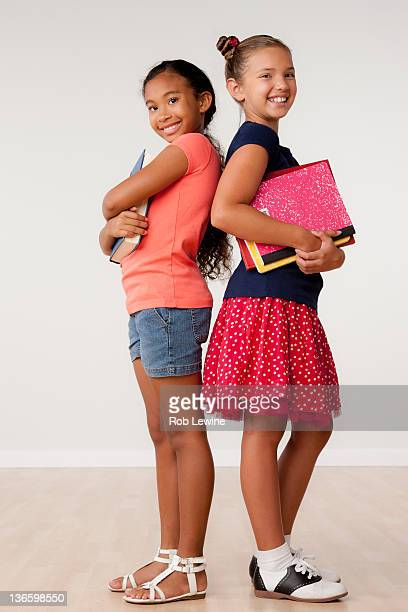Studio portrait of two girls (8-9) holding books