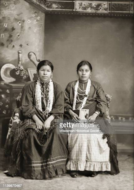 Studio portrait of two HoChunk women Frieda Blackcoon and Mary Cloud White posing sitting in front of a painted backdrop Black River Falls Wisconsin...