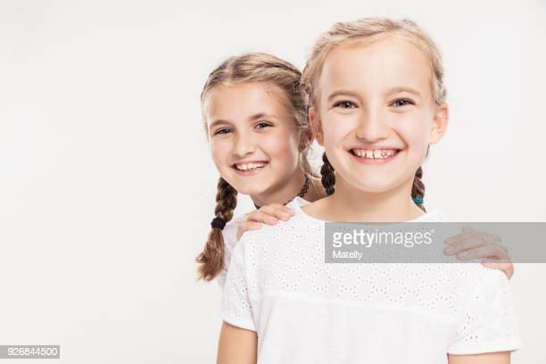 studio portrait of two smiling girls, head and shoulders - high key stock pictures, royalty-free photos & images
