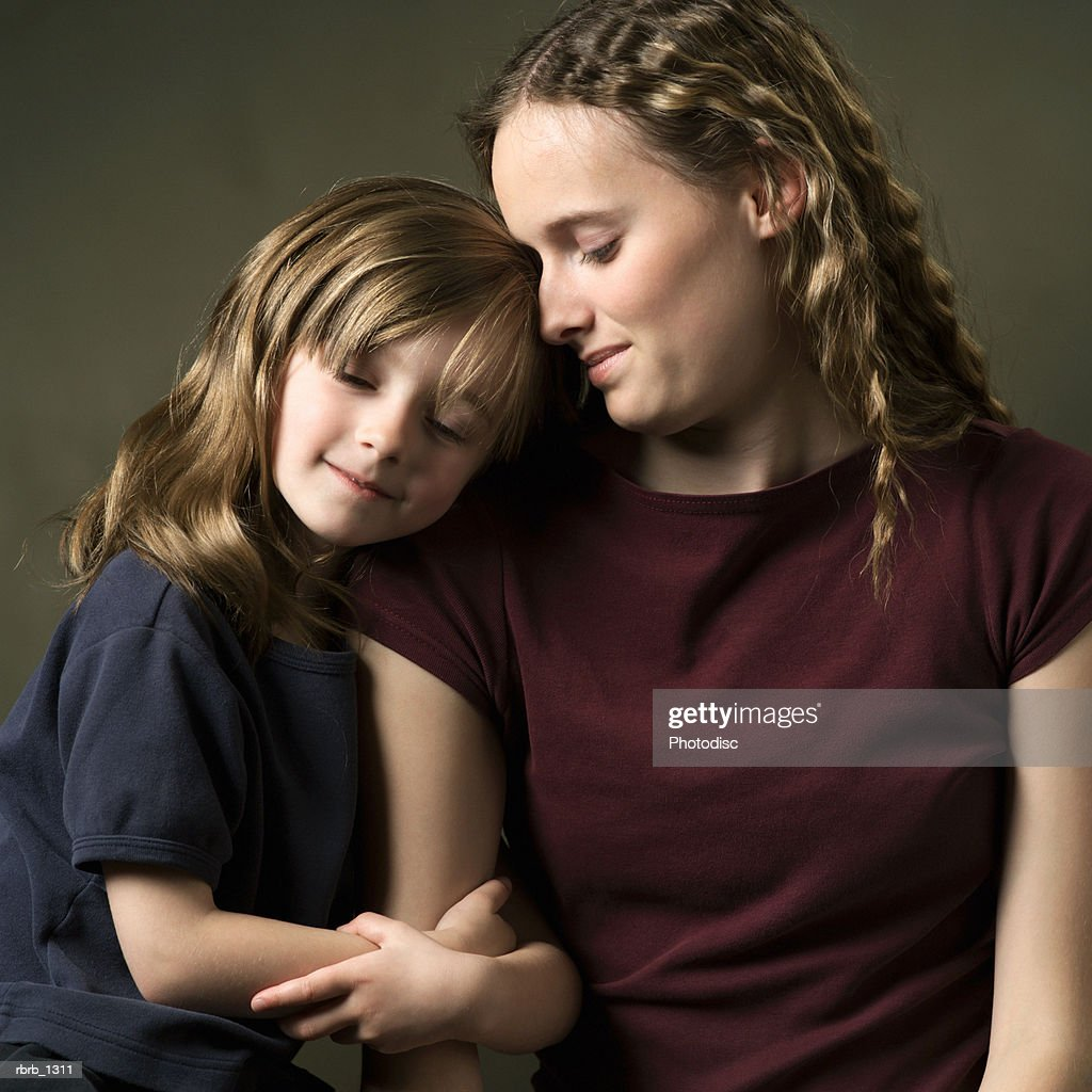 studio portrait of two young caucasian sisters as one rests her head on the others shoulder : Stockfoto