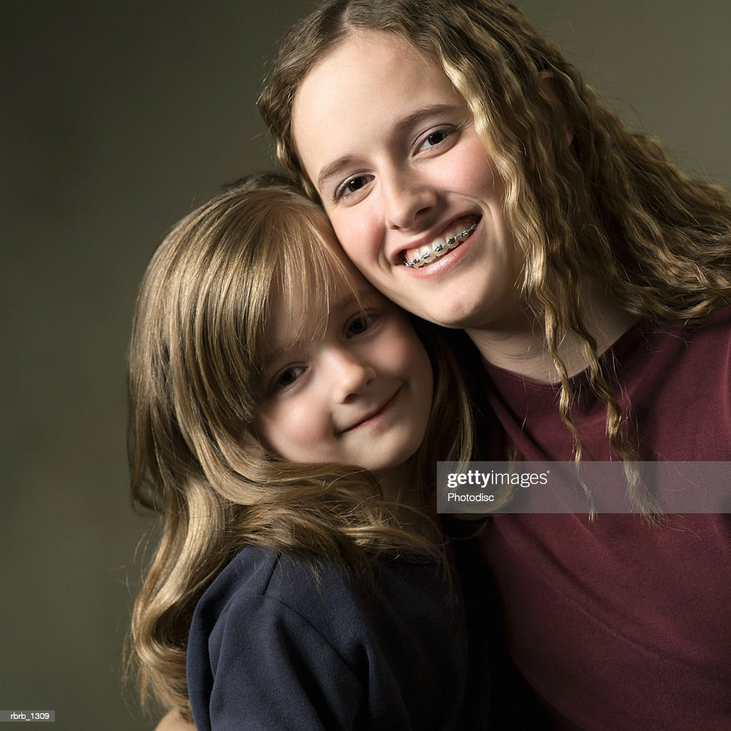 studio portrait of two young caucasian sisters as they embrace and smile together : Stockfoto