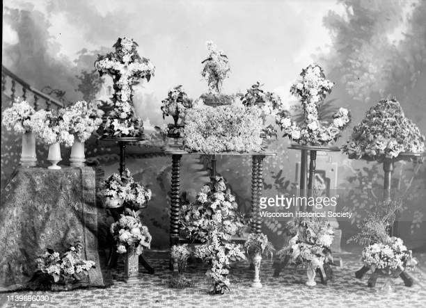 Studio portrait of various bouquet wreaths in several shapes including a cross and anchor in front of a painted backdrop Black River Falls Wisconsin...