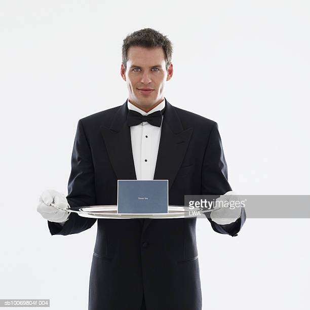 studio portrait of waiter with greeting card on serving tray - タキシード ストックフォトと画像