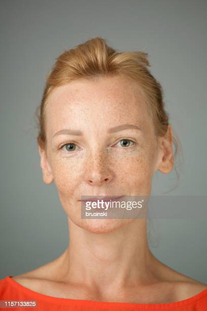 studio portrait of woman blonde with freckles on gray background - northern european stock pictures, royalty-free photos & images